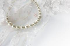 在鞋带背景的美丽的乳脂状的珍珠项链。 免版税库存图片