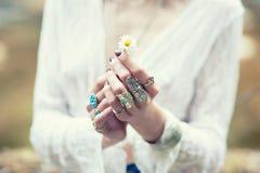 在鞋带衣裳穿戴的Boh别致的装饰品的一个嬉皮女孩拿着一朵雏菊花 葡萄酒滤色器 免版税库存照片