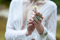 在鞋带衣裳穿戴的Boh别致的装饰品的一个嬉皮女孩拿着一朵雏菊花 免版税库存图片