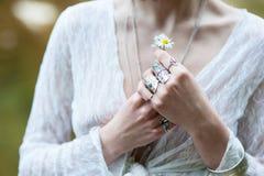 在鞋带衣裳穿戴的Boh别致的装饰品的一个嬉皮女孩拿着一朵雏菊花 库存照片