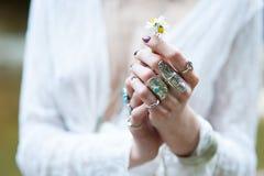 在鞋带衣裳穿戴的Boh别致的装饰品的一个嬉皮女孩拿着一朵雏菊花 免版税图库摄影