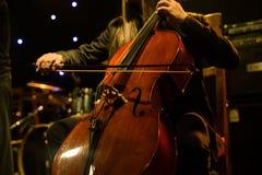 在音乐会期间,供以人员使用在阶段的大提琴 免版税库存照片