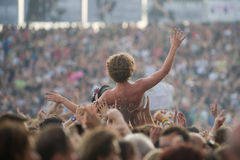 在音乐会期间,一个年轻人由人群上升了 免版税库存图片
