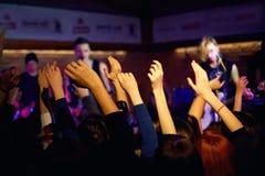 在音乐会的青年挥动的手在夜总会 库存照片