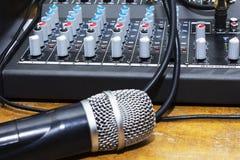 在音乐家的专业冷凝器演播室话筒弄脏了背景和音频搅拌器,乐器概念 免版税库存照片