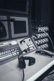 在音乐搅拌器控制台上的耳机在演播室 免版税图库摄影
