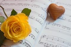 在音乐板料的心脏和黄色玫瑰  免版税库存图片
