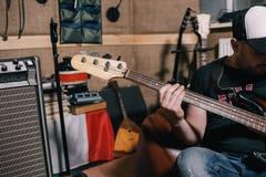 在音乐演播室特写镜头的低音吉他即兴重复段 库存照片