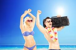 在音乐的激动的夫妇跳舞在海滩 免版税库存图片