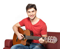 在音响guitat的微笑的吉他弹奏者作用 图库摄影