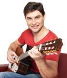 在音响guitat的微笑的吉他弹奏者作用 库存照片