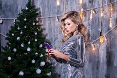在顶楼公寓的少妇谈的手机 拿着电话的时髦的妇女看屏幕圣诞树点燃 季节性 免版税库存图片
