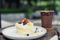 在顶面南瓜籽的草莓和蓝莓蛋糕与被冰的椰树 免版税图库摄影