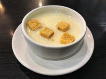 在顶面玉米汤的饼干在黑木桌上的白色碗 免版税库存照片