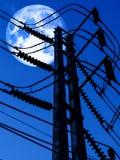 在顶面输电线柱子的超级月亮后面阴影 库存照片