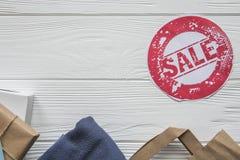 在项目的折扣在牛仔布样式的白色木背景与红色标签 免版税库存照片