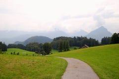 在领域与房子和山之间的路在背景 免版税库存照片