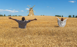 在领域中的愉快的夫妇用成熟的谷物 免版税图库摄影