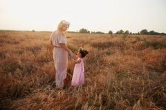 在领域和女儿跑的母亲 长的礼服 库存照片