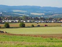 在领域和山之间的村庄 库存照片
