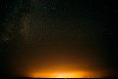 在领域和黄灯上的夜满天星斗的天空在背景 晚上 免版税库存图片