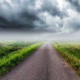 在领域和暴风云的乡下公路 免版税库存图片