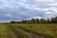 在领域导致村庄的,在内地俄国人的金黄秋天的乡下公路, Kostroma地区 库存图片