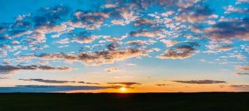在领域或草甸的日落日出 明亮的剧烈的天空和黑暗的地面 库存图片
