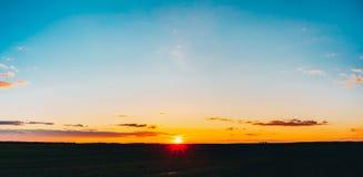 在领域或草甸的日落日出 明亮的剧烈的天空和黑暗的地面 图库摄影