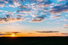 在领域或草甸的日落日出 明亮的剧烈的天空和黑暗的地面 免版税库存照片