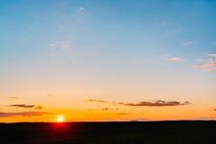 在领域或草甸的日落日出 明亮的天空和黑暗的地面 免版税库存图片