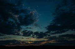 在领域或草甸的自然日落日出 明亮的剧烈的天空和黑暗的地面 免版税库存照片