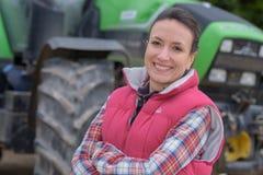 在领域拖拉机的年轻女性agricultor在背景中 图库摄影