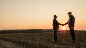 在领域握手上的两位农夫在日落 宽透镜射击 免版税库存图片