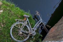 在领域放弃的生锈老自行车说谎,沿水 免版税图库摄影