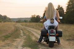 在领域的一对年轻夫妇在摩托车旁边 免版税库存照片