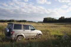 在领域的俄国UAZ SUV 免版税库存照片
