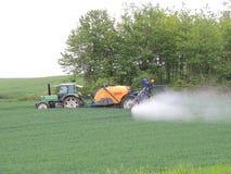 在领域的农夫喷洒的化学制品 免版税库存图片