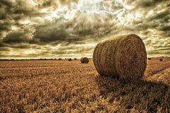 在领域的干草捆在恼怒的天空2下 库存照片