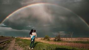 在领域的彩虹与人 妈妈和儿子看看彩虹 免版税库存图片