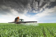 在领域的拖拉机喷洒的麦子 免版税库存照片