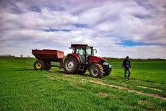 在领域的拖拉机工作 在春天应用肥料 库存图片