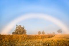 在领域的早晨雾与上面一条白色彩虹 库存照片