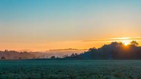 在领域的有薄雾的早晨日出 库存照片