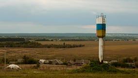 在领域的村庄watertower 免版税图库摄影