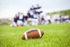 在领域的橄榄球球 免版税库存照片