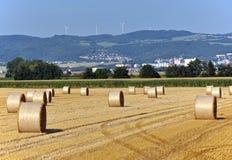 在领域的秸杆大包与城市和风轮机在背景中 图库摄影