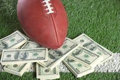 在领域的美国橄榄球联盟橄榄球与一堆金钱 免版税库存照片