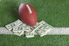 在领域的美国橄榄球联盟橄榄球与一堆金钱 库存照片