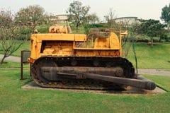 在领域的老黄色生锈的履带拖拉机 在绿色庭院的老履带拖拉机 库存图片